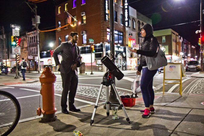 Bill Green (left) dispenses moon facts to revelers at 4th and South Streets. (Kimberly Paynter/WHYY)