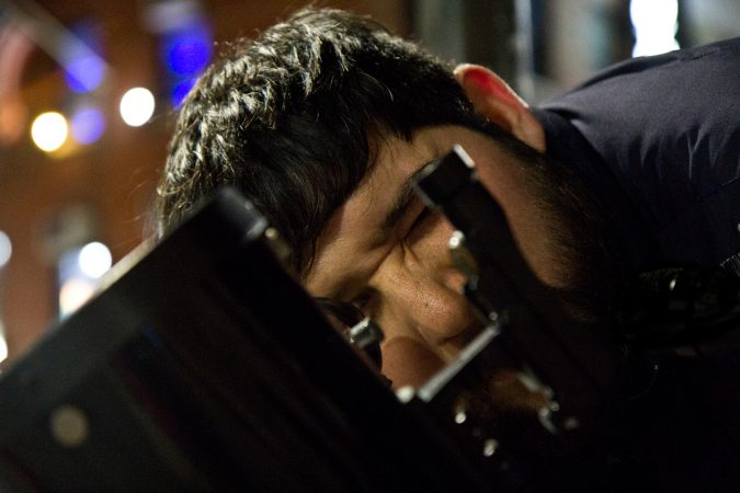 Abraham Reyes looks through a telescope on South Street. (Kimberly Paynter/WHYY)