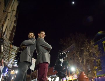 Bill Green (left) and Brendan Happe are amateur astronomers who invite people on the streets of Philadelphia to gaze at the moon through a telescope. (Kimberly Paynter/WHYY)