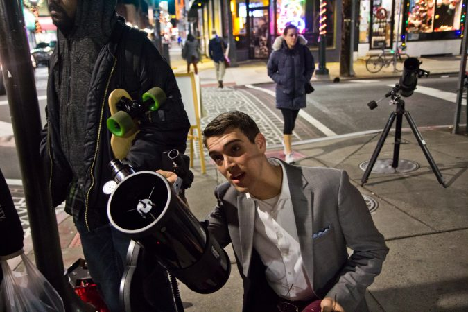 Brendan Happe adjusts the moon gazing telescope at 4th and South Streets in Philadelphia. (Kimberly Paynter/WHYY)