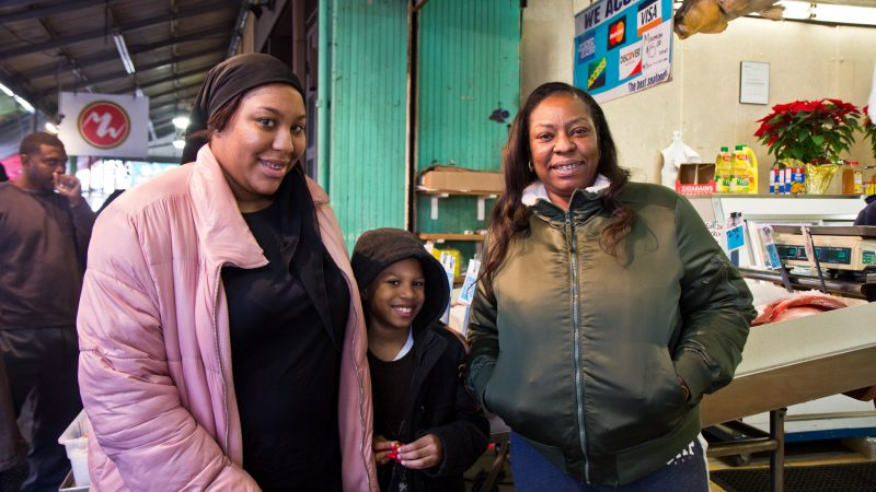 Tracey Prioleau (right) and her family shop for Christmas fish at Marcos in the Italian Market. (Kimberly Paynter/WHYY)