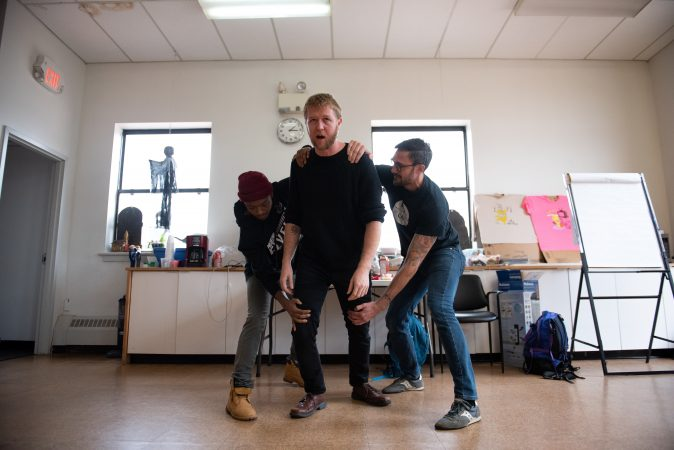 Mark Kennedy (center) struggles to move forward while being held back by Omi Masika (left) and Toby Fraser (right) during an exercise at a masculinity workshop held at Lutheran Settlement House on Sunday, October 28, 2018. (Kriston Jae Bethel for WHYY)