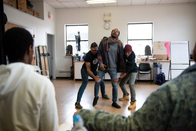 Dwight Dunston (center) drags himself forward as Toby Fraser (left) and Omi Masika (right) hold him back during an exercise at a masculinity workshop held at Lutheran Settlement House on Sunday, October 28, 2018. (Kriston Jae Bethel for WHYY)