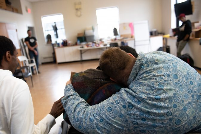 Curtis Walker embraces Dwight Dunston following an exercise where Dunston shouted what change he wanted to see during an exercise at a masculinity workshop held at Lutheran Settlement House on Sunday, October 28, 2018. (Kriston Jae Bethel for WHYY)