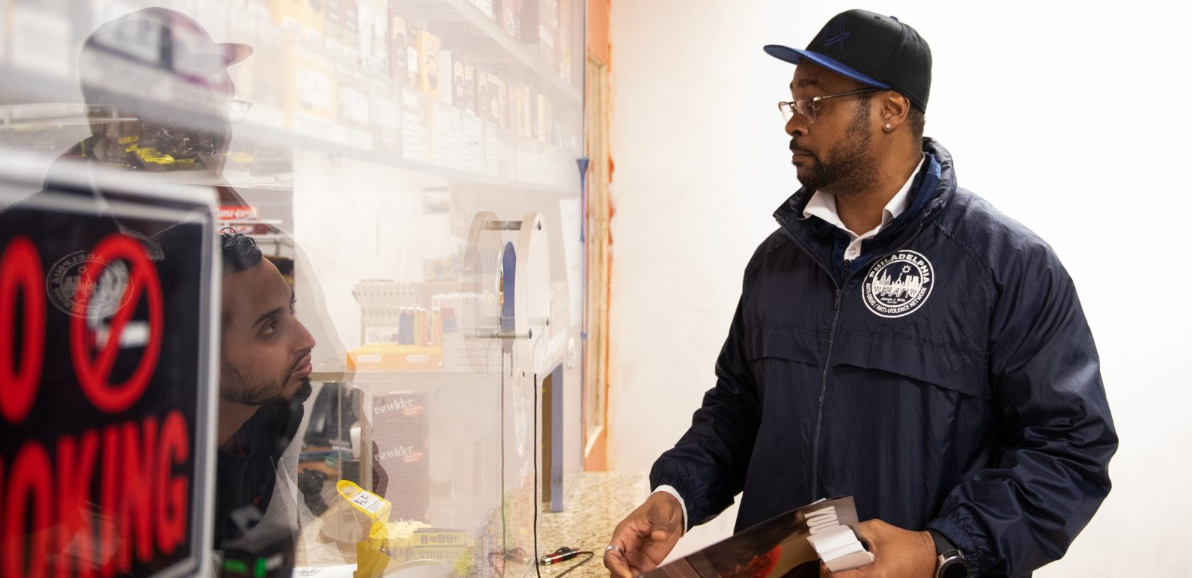 Tarik Harris talks to Sam, who's working the counter at the Logan Food Mini Market, about how CCIP can help businesses who are experiencing concerns of violence. (Kriston Jae Bethel for WHYY)