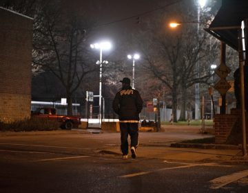 While canvassing in Olney, Tarik Harris crosses the street to survey Lindley Playground, which he says is known to be a location for selling drugs. (Kriston Jae Bethel for WHYY)