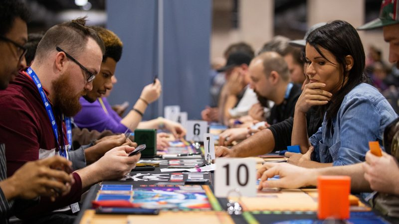 Jon Phillips and Jessica Rodriguez play the card game Lightseekers at PAX Unplugged on Friday, November 30, 2018. (Kriston Jae Bethel for WHYY)