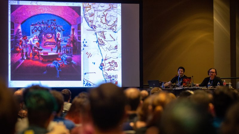 Authors Michael Witwer and Jon Peterson discuss original artwork from a 1980s version of Dungeons & Dragons during a presentation on the visual history of the popular roleplaying game. (Kriston Jae Bethel for WHYY)