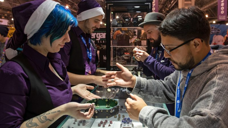 Edwin Morales takes a die out for a test roll at Level Up Dice, one of the many vendors on display at PAX Unplugged. (Kriston Jae Bethel for WHYY)