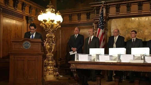 Members of the commission that studied the pension, standing behind binders full of documents. (Katie Meyer/WITF)