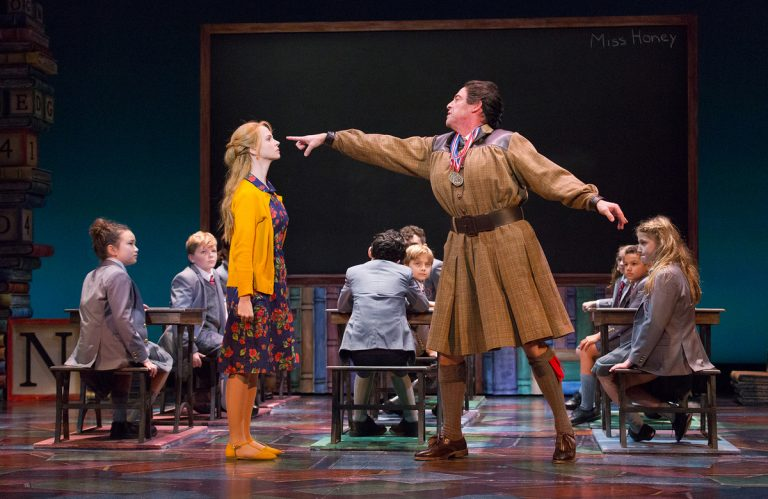 Laura Giknis as a first-grade teacher, Ian Merrill Peakes as Miss Trunchbull, and Jemma Bleu Greenbaum (far right), one of two actresses who play Matilda on different nights in the Walnut Street Theatre production of the musical