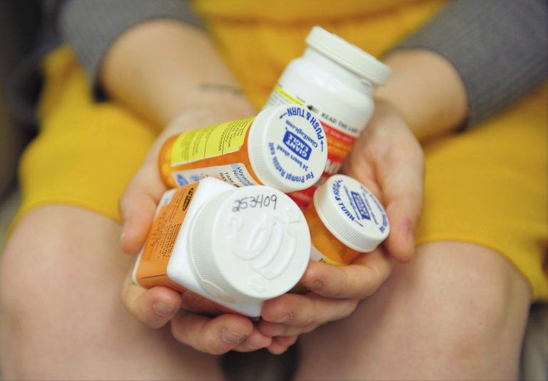 Heidi Wyandt, 27, holds a handful of her medication bottles at the Altoona Center for Clinical Research in Altoona, Pa., on Wednesday, March 29, 2017, where she is helping test an experimental non-opioid pain medication for chronic back pain related to a work related injury she received in 2014. (Chris Post/AP Photo)