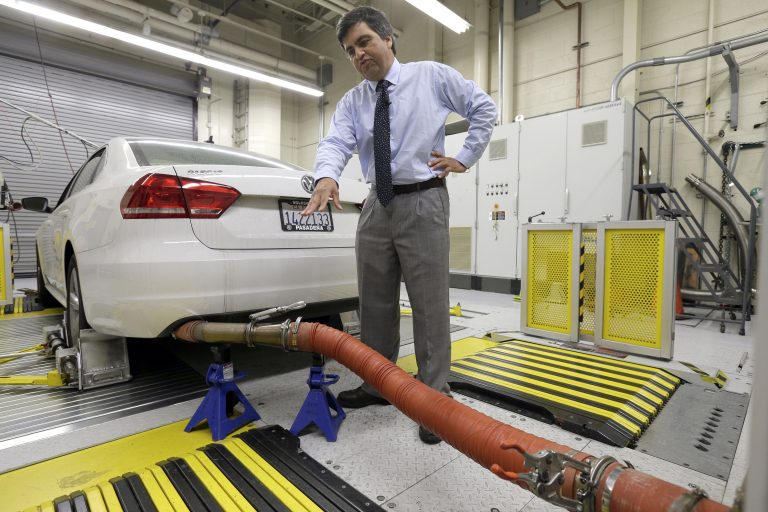 In this Sept. 30, 2015, file photo, John Swanton, spokesman with the California Air Resources Board, explains how a 2013 Volkswagen Passat with a diesel engine is evaluated at the emissions test lab in El Monte, Calif. California officials on Friday, Oct. 26, 2018, blasted the Trump administration's plan to freeze vehicle emissions standards, saying it threatens public health and the environment and was based on a flawed scientific analysis. (Nick Ut/AP Photo, File)