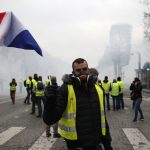 A demonstrator waves a French flag on the Champs-Elysees avenue Saturday, Dec. 8, 2018 in Paris. Crowds of yellow-vested protesters angry at President Emmanuel Macron and France's high taxes tried to converge on the presidential palace Saturday, some scuffling with police firing tear gas, amid exceptional security measures aimed at preventing a repeat of last week's rioting. (Rafael Yaghobzadeh/AP)