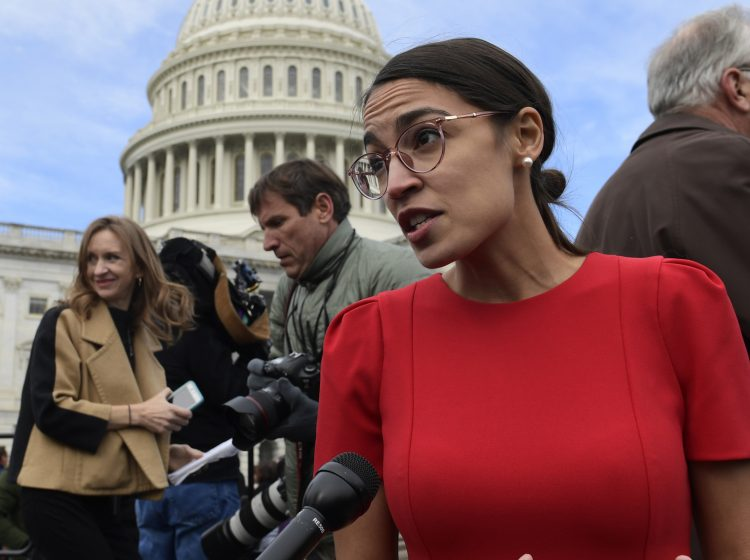In this Nov. 14, 2018 photo, Rep.-elect Alexandria Ocasio-Cortez, D-N.Y., talks with reporters following a photo opportunity on Capitol Hill in Washington.  While tea party Republicans swept to power to stop things -- repeal Obamacare, roll back environmental regulations and decrease the size and scope of government -- Democrats are marching into the majority to build things back up. And after spending eight downcast years in the minority, they can't wait to get started. (AP Photo/Susan Walsh)