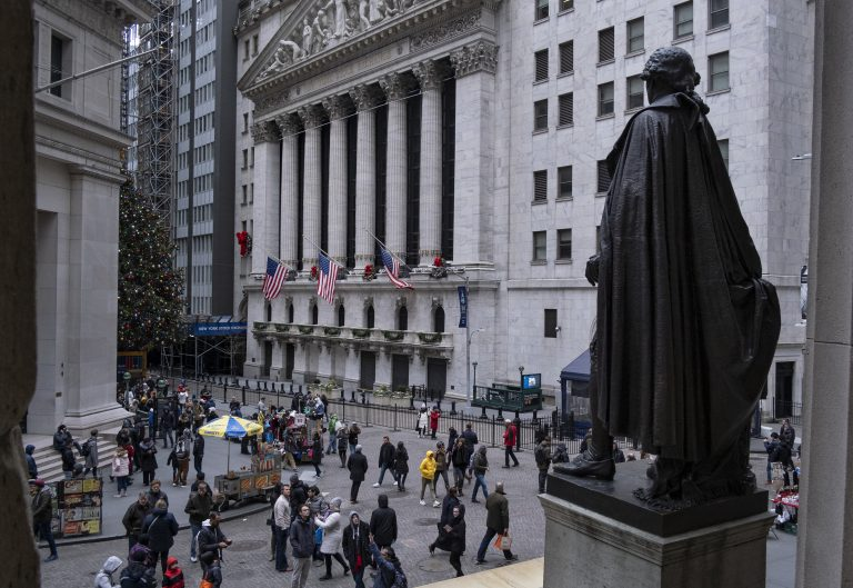 People stand near a statue of George Washington, adjacent to the New York Stock Exchange, background, Saturday, Dec. 22, 2018, at the closed Federal Hall National Memorial in New York.   Now in its 10th year, America's economic expansion still looks sturdy. Yet the partial shutdown of the government that began Saturday has added another threat to a growing list of risks. (Craig Ruttle/AP Photo)