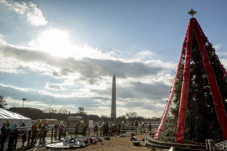 Visitors to the National Christmas Tree on the Ellipse look at holiday decorations as National Park Service employees briefly open the venue before quickly having to close again due to electrical problems, Monday, Dec. 24, 2018, in Washington. Repairs were delayed because of a partial government shutdown. Both sides in the long-running fight over funding President Donald Trump's U.S.-Mexico border wall appear to have moved toward each other, but a shutdown of one-fourth of the federal government entered Christmas without a clear resolution in sight. (Andrew Harnik/AP)