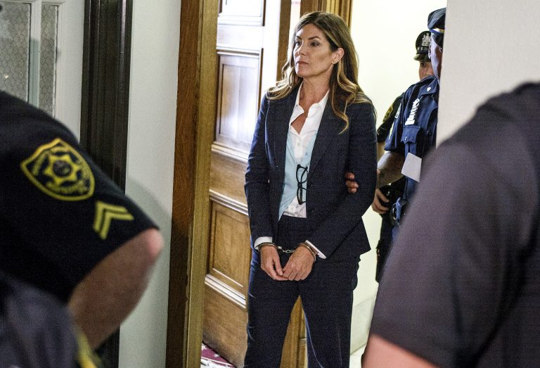 Former Pennsylvania Attorney General Kathleen Kane leaves court in handcuffs after her sentencing at the Montgomery County Courthouse in Norristown, Pa., Monday, Oct. 24, 2016. Kane was sentenced to 10-to-23 months in county jail and 8 years probation. In August 2016, Kane was found guilty of felony perjury and an assortment of misdemeanors related to a leak of secret grand jury materials. (Dan Gleiter/PennLive.com via AP, Pool)