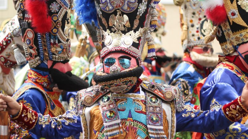 Participants in elaborate costumes dance on Washington Avenue in South Philadelphia to celebrate the annual Carnaval de Puebla on April 29, 2018. The celebration of Mexican culture and history honors Mexico's victory in the Battle of Puebla in 1862. (Angela Gervasi for WHYY)