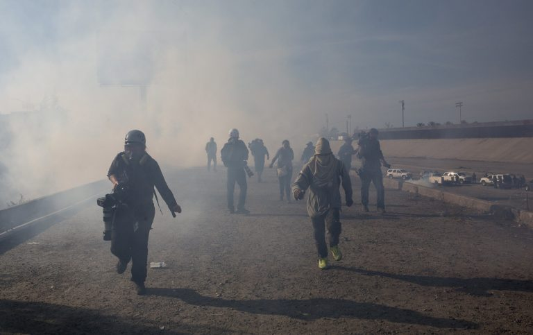 Migrants run from tear gas launched by U.S. agents, amid photojournalists covering the Mexico-U.S. border, after a group of migrants got past Mexican police at the Chaparral crossing in Tijuana, Mexico, Sunday, Nov. 25, 2018. (AP Photo/Rodrigo Abd)
