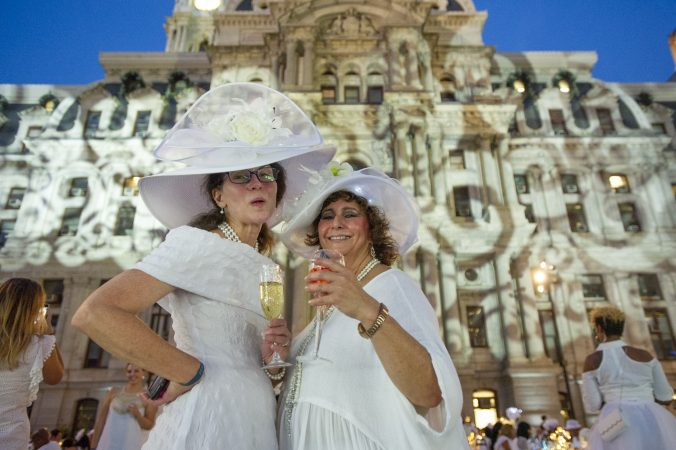 Zarbeth Teelucksingh (right) and a friend show off their hats at Le Dîner en Blanc on Aug. 16, 2018. (Jonathan Wilson for WHYY)