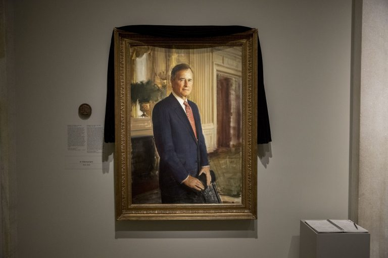 The official portrait of former President George H.W. Bush is draped in black cloth at the National Portrait Gallery in Washington, Monday, Dec. 3, 2018, to mark his passing. Bush will lay in state at the Capitol building this week before being buried in Texas. (AP Photo/Andrew Harnik)