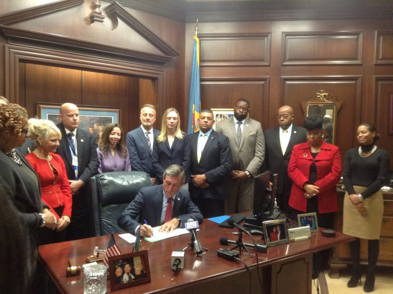 Delaware Gov. John Carney signs an executive order Tuesday aimed at reducing recidivism. (Zoe Read/WHYY)