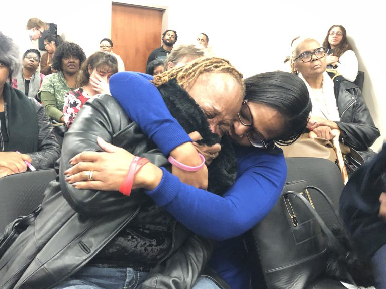 Sharon Osburn (left) fights back tears after telling prison officials about her son's sudden transfer to a Pennsylvania prison. Osburn is being comforted by state Rep. Sherry Dorsey Walker of Wilmington. (Cris Barrish/WHYY)