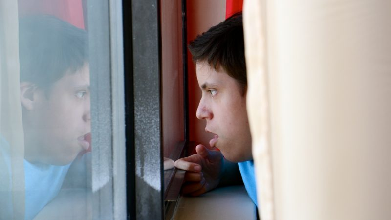 Luis Angel Chaparro Crespo, 16, watches the trains go by from the window of his apartment on the sixth floor of the Harrison Homes in North Philadelphia. He and his parents left Puerto Rico after Hurricane Maria because he needed surgery that could no longer be provided at home. (Emma Lee/WHYY)