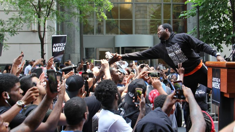Meek Mill reaches out to supporters outside the Criminal Justice Center on June 18, 2018, before his hearing to ask for a new trial on 10-year-old gun and drug charges. (Emma Lee/WHYY)