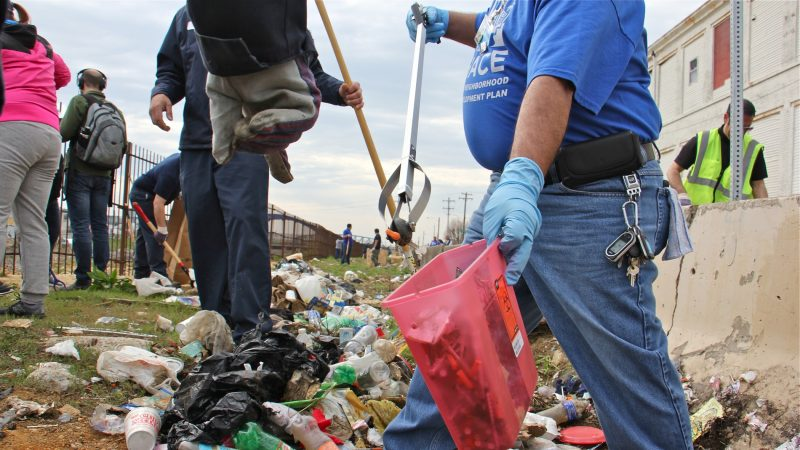 Tony Beltram of HACE separates the syringes from the rest of the trash on April 13, 2018, during the clean-up of a block-long stretch of grass between Gurney Street and the Conrail tracks, which once hosted a heroin encampment. (Emma Lee/WHYY)