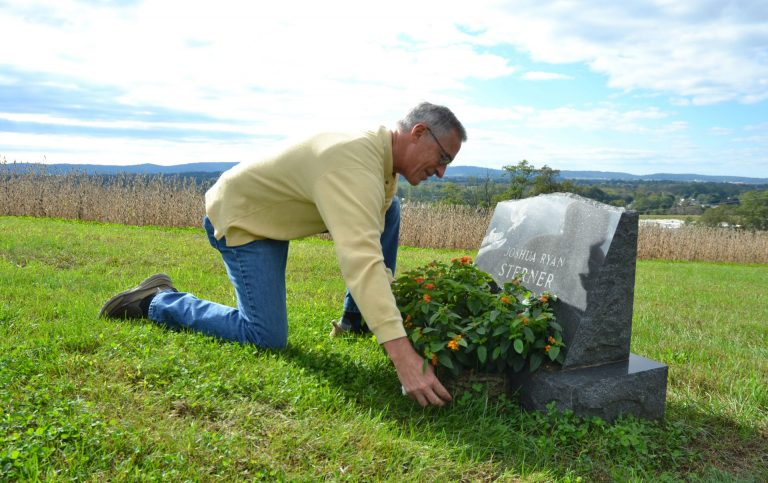 Jeff Sterner adjusts a flower display on his son Joshua's grave. Josh was 19 in 2012 when he died by suicide. (Brett Sholtis / Transforming Health)