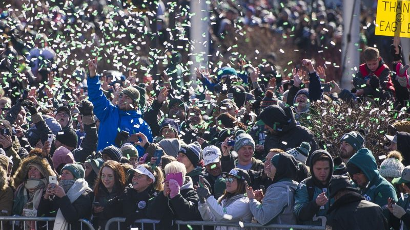 Fans are showered with confetti from passing team buses during the Super Bowl parade in Philadelphia, Feb. 8, 2018. (Jonathan Wilson for WHYY)