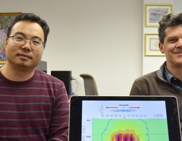 Tieyuan Zhu, (left), and Eugene Morgan of Pennsylvania State University are part of a research team studying carbon storage. They are pictured here with a model that helps explain how carbon dioxide moves through rock underground. (Amy Sisk/StateImpact Pennsylvania)