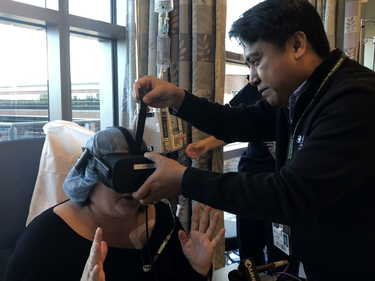 Christine Jacono has her virtual reality headset adjusted by software engineer Erwin Bautista during a December chemotherapy treatment at Christiana Care's cancer center. (Cris Barrish/WHYY)
