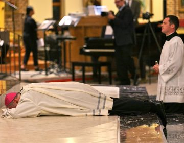 Bishop Dennis Sullivan prostrates himself at the altar during an evening of prayer for the victims of sexual abuse by Catholic clergy on Sept. 28, 2018, in Blackwood, New Jersey. (Miguel Martinez for WHYY)