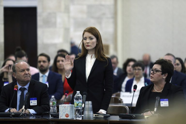 In December 2018, Katie Brennan, the chief of staff at the New Jersey Housing and Mortgage Finance Agency, raises her hand as she is sworn in to testify before the Select Oversight Committee at the Statehouse in Trenton, N.J. Brennan, a top staffer at the state's housing agency came forward as sexual assault victim and has said too little was done about her complaints, which she reported to law enforcement. (Mel Evans/AP Photo)
