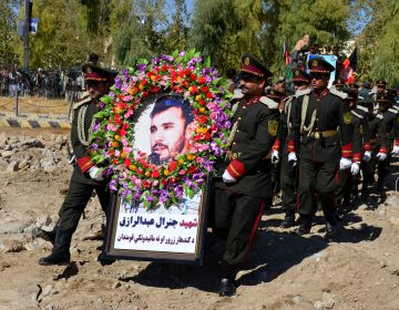 Guards of honor carry a photo of Brig. Gen. Abdul Raziq, Kandahar police chief, at his burial ceremony in Kandahar in October. (AP)
