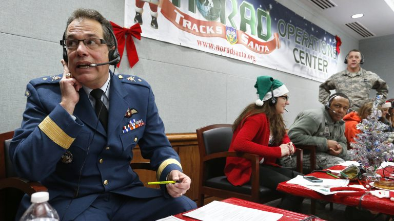 Every year, NORAD staff and volunteers field calls from children inquiring about Santa. Canadian Brig. Gen Guy Hamel joined in the tradition in 2014. (Brennan Linsley/AP)