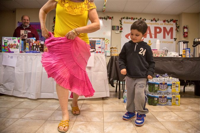 Five-year-old Jose Marlon learns how to dance a traditional dance from Puerto Rico at APM's Three Kings Day/Octavious celebration for diplaced families from Puerto Rico in North Philadelphia on January 12, 2018. (Emily Cohen for WHYY)
