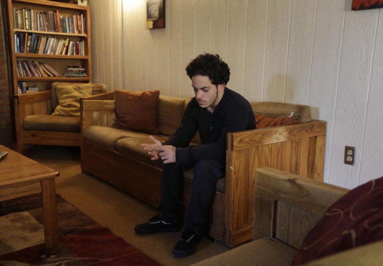 In this Thursday, April 24, 2014 photo, Jose Osario, 20, a resident of the transition cottage, sits in the living room of another cottage at the Children's Village campus in Dobbs Ferry, N.Y. (AP Photo/Seth Wenig)