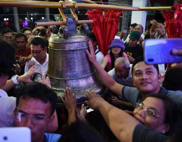Residents take photos and try to touch one of the three Balangiga church bells after a ceremony returning them to the church in the town of Balangiga in the Philippines on Dec. 15, 2018. (Ted Aljibe/AFP/Getty Images)