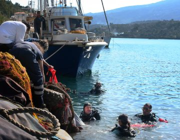 Aegean Rebreath founder George Sarelakos (center) hands a netted bag of marine litter to volunteers on the main pier of the Greek island of Poros. (Joanna Kakissis for NPR)