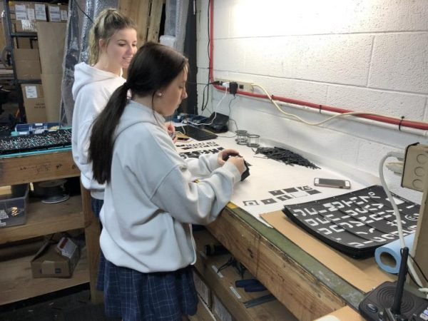 Megan Smith and Mackenzie Waters, assembly technicians at Oat Foundry and sophomores at Nazareth Academy in Philadelphia, snap out printed characters that will be used to build a split-flap display. (Meir Rinde for PlanPhilly)
