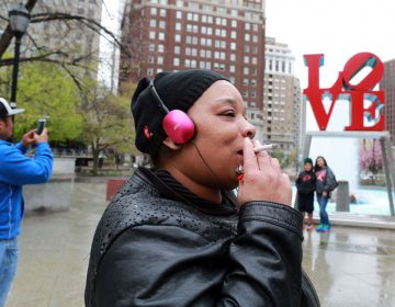 A woman smokes a cigarette at JFK Plaza (David Swanson/Philadelphia Inquirer)