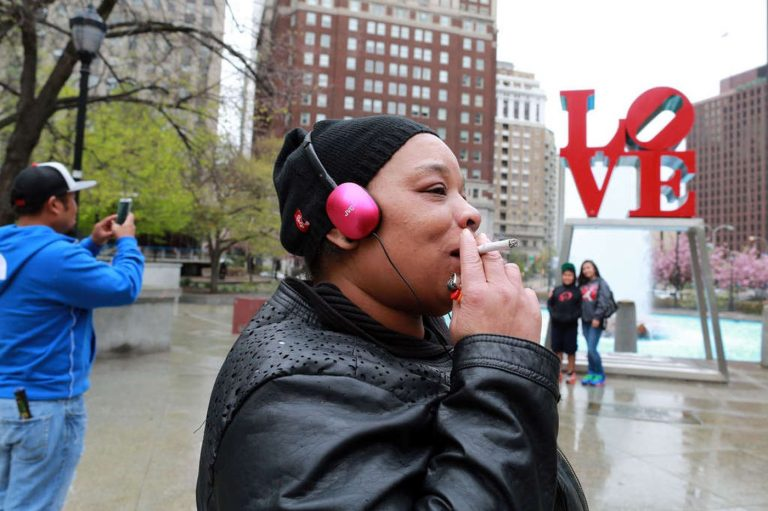 A woman smokes a cigarette at JFK Plaza (David Swanson/Philadelphia Inquirer)