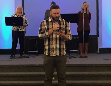 Youth pastor Kyle Smith of First Assembly of God Paradise reads from the Bible on his phone because his copy of the book burned in the Camp Fire. His congregation is one of several now worshiping with congregations in Chico. (Polly Stryker/KQED)