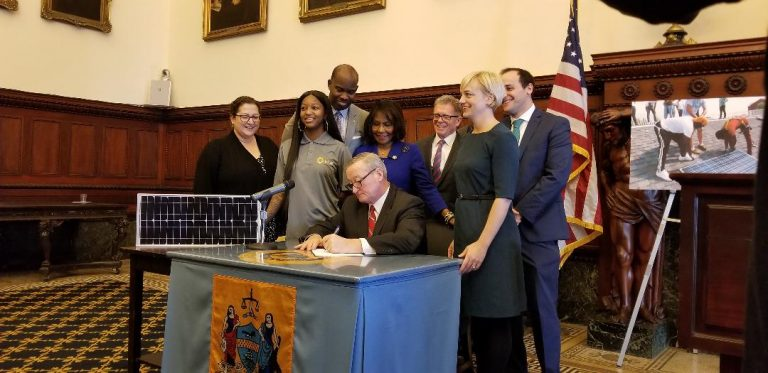 Mayor Jim Kenney signs a bill Tuesday authorizing the Philadelphia Energy Authority — an independent municipal authority set up specifically to reduce the city's energy's consumption — to enter into a contract to purchase 22 percent of its power from solar provider Community Energy. (Tom MacDonald/WHYY)