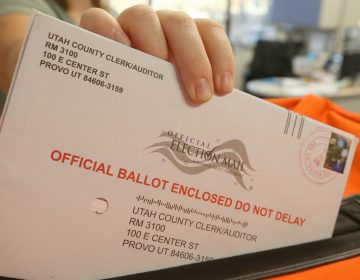 An employee at the Utah County Election office puts mail in ballots into a container to register the vote in the midterm elections on November 6. (George Frey/Getty Images)