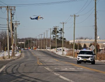 A state police helicopter lands near a UPS facility in Logan Township where two women were held hostage by a gunman. (Emma Lee/WHYY)